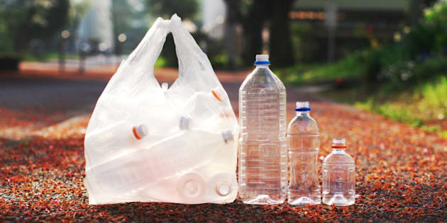 A bag of PET bottle and three loose PET bottles ready to be taken to recycle bin.