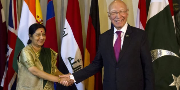Indian Foreign Minister Sushma Swaraj, left, shakes hand with Pakistani Prime Minister's adviser for Foreign Affairs Sartaj Aziz, right, prior to their meeting in Islamabad, Pakistan, Wednesday, Dec. 9, 2015. Swaraj told a news conference that India and Pakistan had agreed to resume talks, which have been on hold since August when Aziz suspended his visit to India over the issue of Kashmir. (AP Photo/Anjum Naveed)