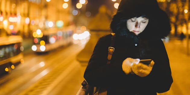 Woman in winter clothing texting in an urban scene.