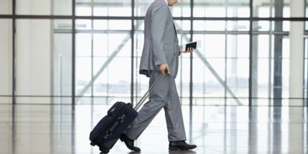 Low section of businessman walking at airport