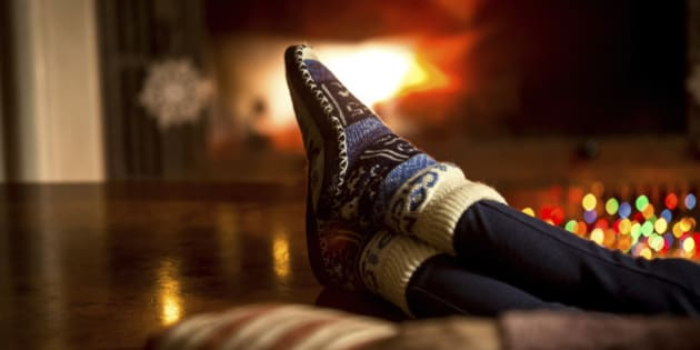 Closeup portrait of feet at woolen socks warming at fireplace in winter