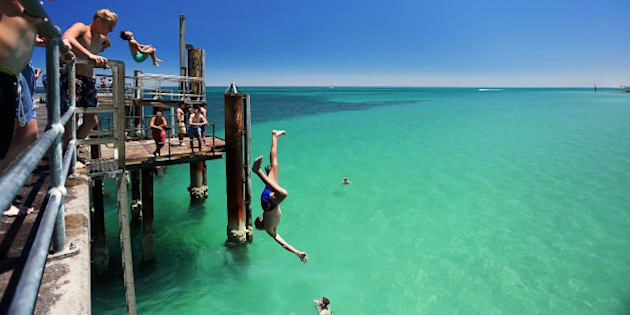 ADELAIDE, AUSTRALIA - JANUARY 13: A teengager jumps off the Glenelg jetty during a heat wave at Glenelg Beach on January 13, 2014 in Adelaide, Australia. Temperatures are expected to be over 40 degrees celsius all week with health authorities warning the young and elderly to remain indoors.  (Photo by Daniel Kalisz/Getty Images)