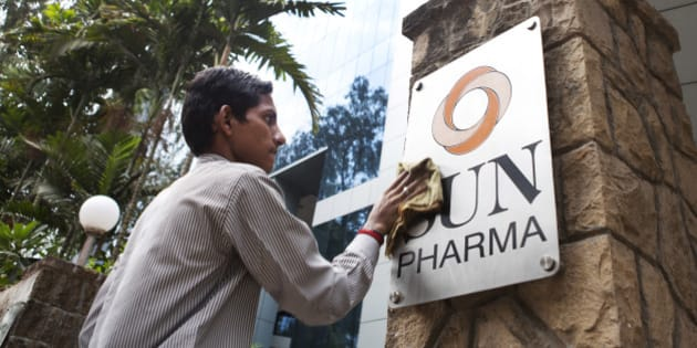 An employee cleans a sign outside the Sun Pharmaceutical Industries Ltd. corporate office in the Andheri suburb of Mumbai, India, on Monday, April 7, 2014. Sun Pharmaceutical, India's largest drugmaker by market value, agreed to buy Ranbaxy Laboratories Ltd. for $3.2 billion in stock, the biggest purchase by an Indian company in two years. Photographer: Amit Madheshiya/Bloomberg via Getty Images