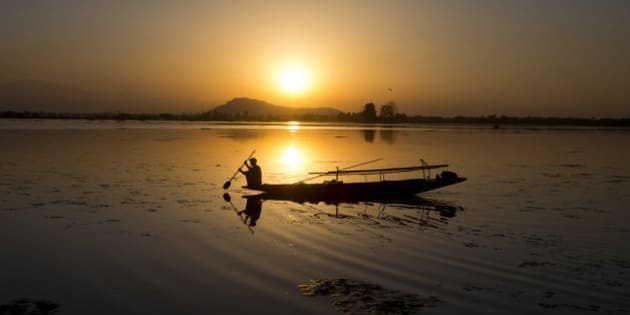 A Kashmiri fisherman rows his Shikara, or traditional boat, during sunset at the Dal Lake in Srinagar, Indian controlled Kashmir, Saturday, Aug. 29, 2015. Nestled in the Himalayan mountains and known for its beautiful lakes and saucer-shaped valleys, the Indian portion of Kashmir, is also one of the most militarized places on earth. (AP Photo/Dar Yasin)