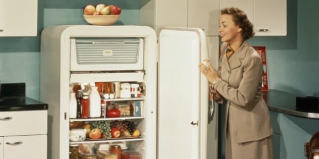 WOMAN APPRECIATING HER STOCKED REFRIGERATOR