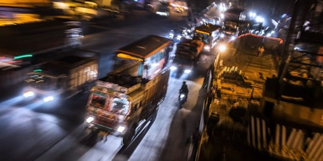 To go with Climate-warming-UN-COP21-India,FOCUS by Trudy Harris  In this November 16, 2015 photo, several cargo trucks make their way down an avenue near midnight in New Delhi. It is estimated that about 80,000 trucks transit through the heart of the city every night from 8 pm to 6 am. India's capital, with 18 million residents, has the world's most polluted air with six times the amount of small particulate matter (pm2.5) than what is considered safe, according to the World Health Organization (WHO). The air's hazardous amount of pm2.5 can reach deep into the lungs and enter the blood, causing serious long term health effect, with the WHO warning India has the world's highest death rate from chronic respiratory diseases. India, home to 13 of the world's top 20 polluted cities, is also the third largest emitter of greenhouse gases behind the United States and China. In Delhi, the air pollution is due to vehicle traffic including cargo trucks running on low-grade diesel, individual fires that residents burn in winter, crop being burnt by farmers in neighboring states, and construction site dust. Burning coal in power plants is also major contributor that is expected to increase hugely in the coming decades to match electricity needs of the ever-growing city and its booming satellite towns. AFP PHOTO / ROBERTO SCHMIDT        (Photo credit should read ROBERTO SCHMIDT/AFP/Getty Images)