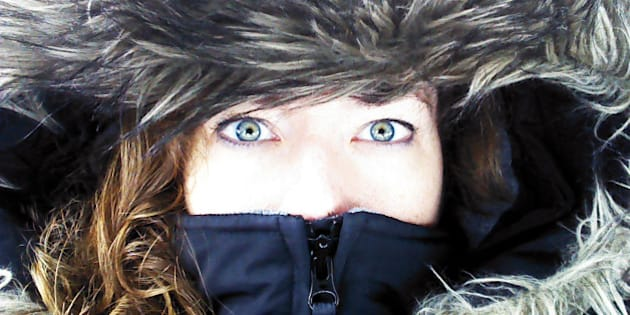 Close up of woman's face, focused on green eyes, zipped inside the hood of a large winter coat or parka, with a fur lining. Cold weather portrait.