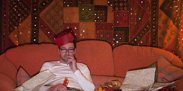 A man wearing a paper hat and surrounded by Christmas wrapping paper, slumps alone on a sofa in front of a TV.
