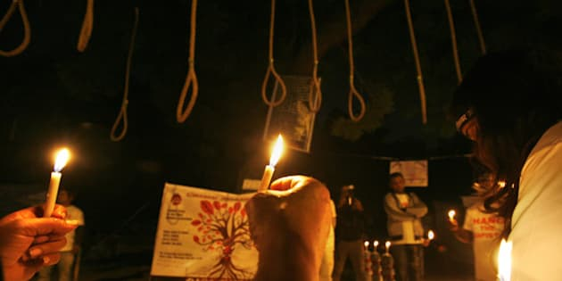 NEW DELHI, INDIA - DECEMBER 16: Indian activists hold candles near hangman's nooses during a candle light march to mark the second anniversary of the fatal gang-rape of a student on December 16, 2014 in New Delhi, India. On December 16, 2012, a 23-year-old physiotherapy student was brutally gang raped and by six men, including a juvenile, in a moving bus. The incident unleashed a wave of public anger over levels of violence against women in the country. (Photo by Arun Sharma/Hindustan Times via Getty Images)