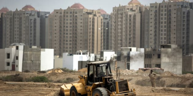 A Caterpillar Inc. digger operates at a construction site next to Creek Vista apartments, background, in Karachi, Pakistan on Sunday, June 28, 2015. The construction boom also marks the nation's emergence as a frontier market after Prime Minister Nawaz Sharif averted a balance-of-payments crisis with help from the International Monetary Fund and resumed selling stakes in state companies. Photographer: Asim Hafeez/Bloomberg via Getty Images