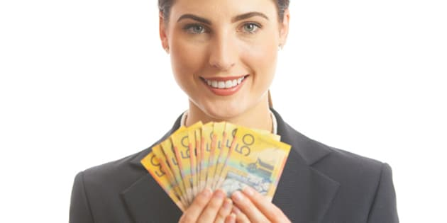 Close up of a happy business woman holding Australian cash. She is dressed in a corporate business suit, and is smiling and looking at camera. Studio shot on a white background.