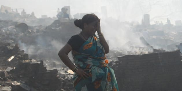 MUMBAI, INDIA - DECEMBER 7: An Indian woman cries as she tries to collect her belongings from the charred remains following a fire at a slum in the east of Kandivali, an area in the north of Mumbai on December 7, 2015. A massive fire sparked by a series of gas cylinder explosions swept through a packed slum in India's Mumbai, killing one person and destroying around 1,000 homes, officials said. (Photo by Imtiyaz Shaikh /Anadolu Agency/Getty Images)