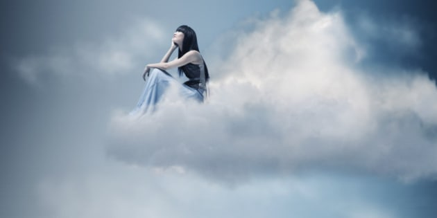 Woman sitting and thinking on a cloud.