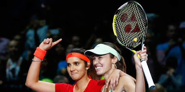 SINGAPORE - NOVEMBER 01:  Sania Mirza of India and Martina Hingis of Switzerland  celebrate defeating Carla Suarez Navarro and Garbine Muguruza of Spain in the doubles final match during the BNP Paribas WTA Finals at Singapore Sports Hub on November 1, 2015 in Singapore.  (Photo by Julian Finney/Getty Images)