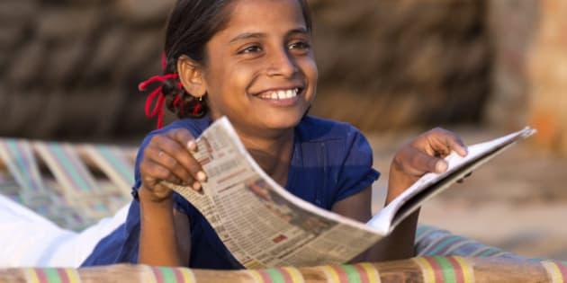 India, Uttar Pradesh, Agra, young girl studying school textbook.