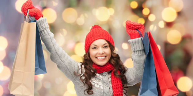 holidays, x-mas, sale and people concept - happy young asian woman in winter clothes with shopping bags over christmas tree lights background