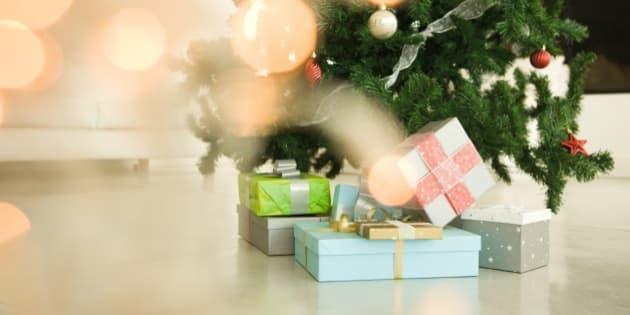 Christmas presents stacked beneath Christmas tree, view through Christmas lights, selective focus