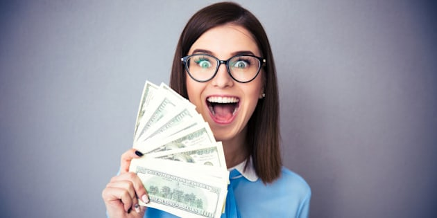 Laughing businesswoman holding bills of dollar and shouting over gray background. Wearing in blue shirt and glasses. Looking at camera