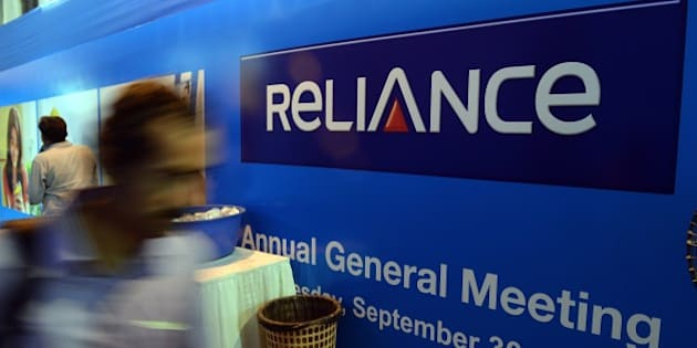 An Indian shareholder walks past a Reliance display at the Annual General Meeting of Reliance Group Companies in Mumbai on September 30, 2015.   AFP PHOTO/ INDRANIL MUKHERJEE        (Photo credit should read INDRANIL MUKHERJEE/AFP/Getty Images)