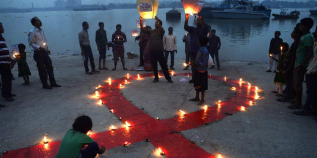 KOLKATA, INDIA - 2015/12/01: Social Activists observe World AIDS Day on the bank of the River Ganges in Kolkata. World AIDS Day is observed on December 01 every year to raise awareness about HIV/AIDS . To generate awareness activist light a big red ribbon and a gas balloons carrying message regarding eradication of stigma and panic discrimination on HIV/AIDS. (Photo by Saikat Paul/Pacific Press/LightRocket via Getty Images)
