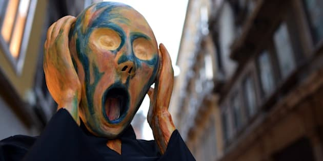 A costumed reveller wearing a mask depicting Munch's famous painting 'The Scream' poses near St Mark's square during the carnival on February 21, 2014 in Venice. The 2014 edition of the Venice carnival is untitled ' Wonder and fantasy nature' and runs from February 15 to March 4, 2014.  AFP PHOTO / GABRIEL BOUYS        (Photo credit should read GABRIEL BOUYS/AFP/Getty Images)