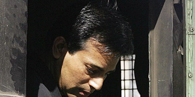 MUMBAI, INDIA:  Alledged Indian gangster Abu Salem looks out from a police van before entering a special court in Mumbai, 23 November 2005.    Salem, alleged to be one of the masterminds of the 1993 serial bombings in the city, has been remanded to judicial custody for 10 days. Salem and his girlfriend Bollywood actress Monica Bedi were extradited to India earlier this month from Portugal . AFP PHOTO/Sebastian D'SOUZA.  (Photo credit should read SEBASTIAN D'SOUZA/AFP/Getty Images)