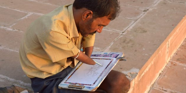 PUSHKAR, RAJASTHAN, INDIA - 2015/09/11: A handicapped artist, Bhagirath Sharma at  Pushkar Ghat is painting a tree. He is from a small village in Nokha. (Photo by Shaukat Ahmed/Pacific Press/LightRocket via Getty Images)