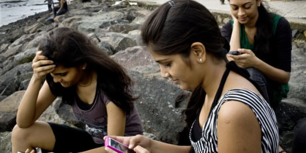 College students Saloni Shah, 18, from left, Roshani Munat, 18 and Shruti Jain, 19, check Facebook Inc. accounts on smartphone devices in Mumbai, India, on Wednesday, Aug. 3, 2011. India has 32 million users of Facebook, according to socialbakers.com, which tracks user data at the Palo Alto, California-based company. Photographer: Kainaz Amaria/Bloomberg via Getty Images
