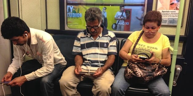 Three commuters comfortably Seated in the subway train Busy working on their electronic device. Milano, Italy