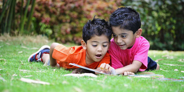 Two kids reading a book, in a park