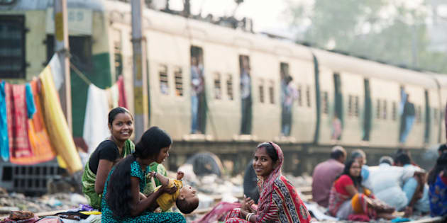 KOLKATA, INDIA - DECEMBER 12:  Women take care of a baby in a slum on the railway tracks as a commuter train goes past on December 12, 2013 in Kolkata, India. Almost one third of the Kolkata population live in slums and a further 70,000 are homeless. (Photo by Samir Hussein/Getty Images)