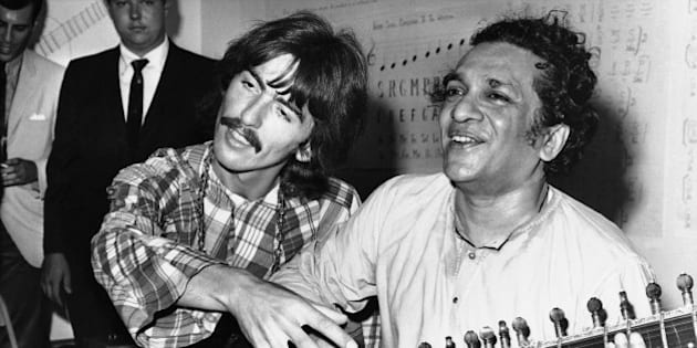 """George Harrison of the Beatles sits cross-legged with his musical mentor, Ravi Shankar of India, a sitar virtuoso, in Los Angeles, Aug. 3, 1967, as Harrison explains to newsmen that Shankar is teaching him to play the sitar, a 25-stringed guitar-like instrument. Harrison said """"Indian music makes God come through in a spiritual way."""" (AP Photo)"""