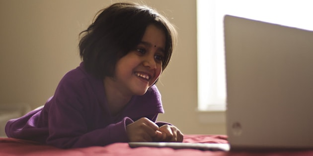 Portrait of a girl child reading through an online homework exercise.