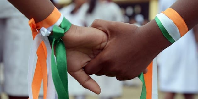 Indian school student hold hands, decorated with the national colours, as they wait to perform during celebrations of India's 68th Independence Day at school in Kolkata on August 15, 2014.  India celebrates its anniversary of independence from Britain on August 15 with great pomp and with the Indian tricolour hoisted atop schools, government offices prominent buildings and homes.  AFP PHOTO/Dibyangshu Sarkar        (Photo credit should read DIBYANGSHU SARKAR/AFP/Getty Images)