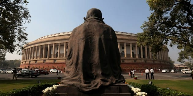 A statue of Mahatma Gandhi overlooks the Indian parliament in New Delhi, India, Monday, Nov. 24, 2014. The winter session of the Indian parliament began Monday. (Staffing/Manish Swarup)