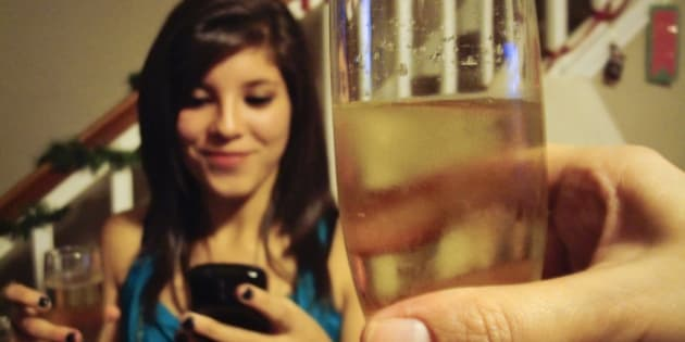 Girl making a toast with champagne in New Year and checking the time in her phone