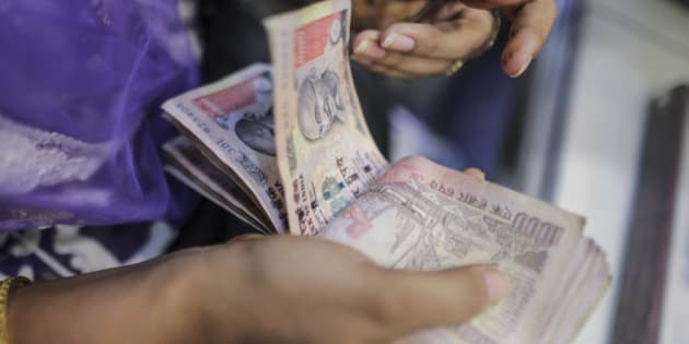 A customer counts Indian rupee banknotes at the Umedmal Tilokchand Zaveri jewelry store during the festival of Dhanteras, two days before Diwali, in the Zaveri Bazaar area of Mumbai, India, on Monday, Nov. 9, 2015. The festival of Dhanteras, which falls on November 9, is the biggest gold-buying day in the year as it is considered to be an auspicious day to purchase bullion. Photographer: Dhiraj Singh/Bloomberg via Getty Images