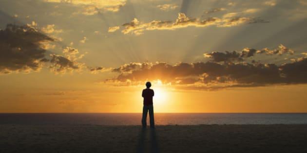 Lone man on the beach watching sunrise