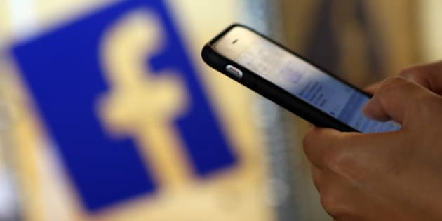 BERLIN, GERMANY - SEPTEMBER 12:  A visitor uses a mobile phone in front of the Facebook logo at the #CDUdigital conference on September 12, 2015 in Berlin, Germany. The world's largest social media network was launched by Mark Zuckerberg and his Harvard College roommates in 2004, and had its initial public offering in February 2012.  (Photo by Adam Berry/Getty Images)