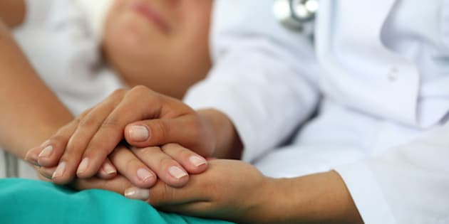Friendly female doctor's hands holding patient's hand lying in bed for encouragement, empathy, cheering and support while medical examination. Trust and ethics concept. Bad news lessening and support