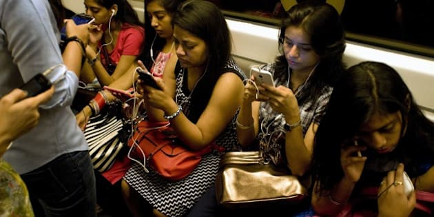 Indian women use their smartphones as they travel in the metro carriage reserved for women in New Delhi on July 14, 2015.  With the first stretch of metro inaugurated in the city in 2002, as of June 2015 the network consists of five regular lines and one express line covering 193 kms and 140 stations.  AFP PHOTO/ Anna ZIEMINSKI        (Photo credit should read ANNA ZIEMINSKI/AFP/Getty Images)