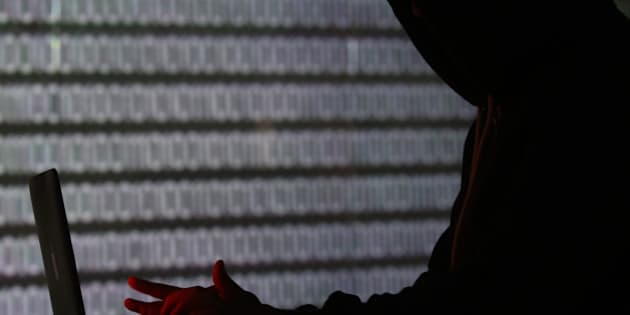 An illuminated wall displays a stream of binary coding, text or computer processor instructions, as a man is seen profiled in silhouette whilst working on a laptop computer in this arranged photograph in London, U.K., on Wednesday, Dec. 23, 2015. The U.K.s biggest banks fear cyber attacks more than regulation, faltering economic growth and other potential risks, and are concerned that a hack could be so catastrophic that it could lead to a state rescue, according to a survey. Photographer: Chris Ratcliffe/Bloomberg via Getty Images