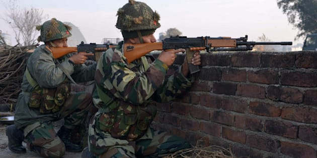 Indian army soldiers take up position on the perimeter of an airforce base in Pathankot on January 3, 2016, during an operation to 'sanitise' the base following an attack by gunmen. The deadly assault on an Indian air base near the Pakistan border was 'a heinous' terrorist attack, the United States said, urging the two rivals to work together to hunt down those responsible. Three security officers were killed in the attack by suspected Islamist militants on Pathankot base in northern Punjab state early January 2. At least four attackers also died in shootouts with security forces. AFP PHOTO/NARINDER NANU / AFP / NARINDER NANU        (Photo credit should read NARINDER NANU/AFP/Getty Images)