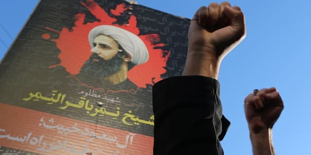 Iranian protesters raise their fists in front of a portrait of prominent Shiite Muslim cleric Nimr al-Nimr during a demonstration against his execution by Saudi authorities, on January 3, 2016, outside the Saudi embassy in Tehran. Iran and Iraq's top Shiite leaders condemned Saudi Arabia's execution of Nimr, warning ahead of protests that the killing was an injustice that could have serious consequences. AFP PHOTO / ATTA KENARE / AFP / ATTA KENARE        (Photo credit should read ATTA KENARE/AFP/Getty Images)