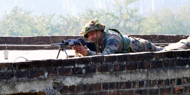 PATHANKOT, INDIA - JANUARY 3: An Indian army soldier takes up position on the perimeter of a Pathankot Airforce Base during an operation to 'sanitise' the base following an attack by gunmen, on January 3, 2016 in Pathankot, India. The deadly assault on an Indian air base near the Pakistan border was 'a heinous' terrorist attack, the United States said, urging the two rivals to work together to hunt down those responsible. Three security officers were killed in the attack by suspected Islamist militants on Pathankot base in northern Punjab state early January 2. So far, six terrorists and seven soldiers, including a Lieutenant colonel, have been killed in the exchange of fire. Five members of the Defence Security Corps succumbed to injuries in the hospital. The attackers were believed to have infiltrated from Pakistan and there was speculation that they may belong to Jaish-e-Mohammad headed by Maulana Masood Azhar of the Kandahar hijack episode (Photo by Sameer Sehgal/Hindustan Times via Getty Images)
