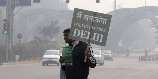 NOIDA, INDIA - JANUARY 1: A Civil Defence personnel holds a placard as he stands at a traffic intersection on the first day of Delhi's Odd-Even Vehicle Plan, on January 1, 2016 in Noida, India. The odd-even scheme that allows odd and even-numbered private vehicles to ply on city roads on alternate days aims at reducing air pollution levels. All diesel and petrol cars, irrespective of where they are coming from, will have to follow the rules. If a car is coming from out of Delhi and is breaking the odd-even rule, a fine will be levied. The government has deployed hundreds of volunteers and 3000 buses to help traffic police. To clean the Capital's toxic air, only odd-numbered private cars will be allowed on the road on odd dates and even-numbered on even days. Violators face a fine of Rs. 2,000. More than a million private cars were banned from New Delhi's roads as authorities began trialling drastic new measures to cut smog in the world's most polluted capital. (Photo by Burhaan Kinu/Hindustan Times via Getty Images)