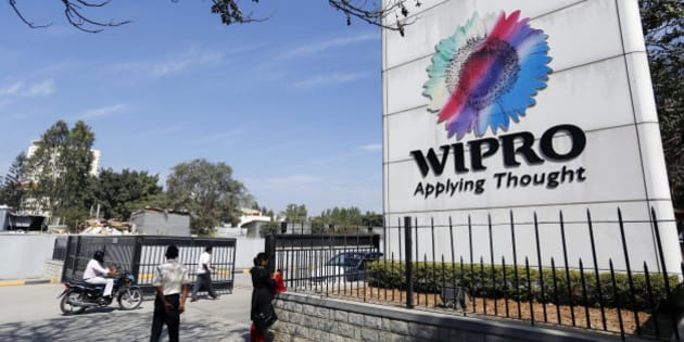 Employees walk past Wipro Ltd. signage as they enter the company's campus in Bangalore, India, on Tuesday, Jan. 28, 2014. Worldwide spending on information technology will grow 3.1 percent to $3.8 trillion this year, with IT services set to climb 4.5 percent, researcher Gartner Inc. forecast Jan. 6. Photographer: Vivek Prakash/Bloomberg via Getty Images