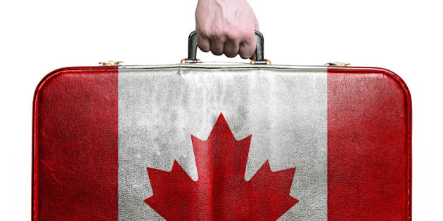 Tourist hand holding vintage leather travel bag with flag of Canada