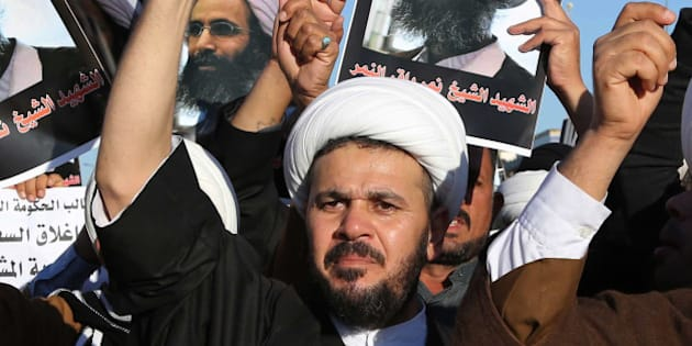 Iraqi Shiite protesters chant slogans against the Saudi government as they hold posters showing Sheikh Nimr al-Nimr, who was executed in Saudi Arabia last week, during a demonstration in Najaf, 100 miles (160 kilometers) south of Baghdad, Iraq, Monday, Jan. 4, 2016. Demonstrations against the al-Nimr execution and Saudi Arabia are also being called for in the predominantly Shiite southern cities on Monday. (AP Photo/Karim Kadim)