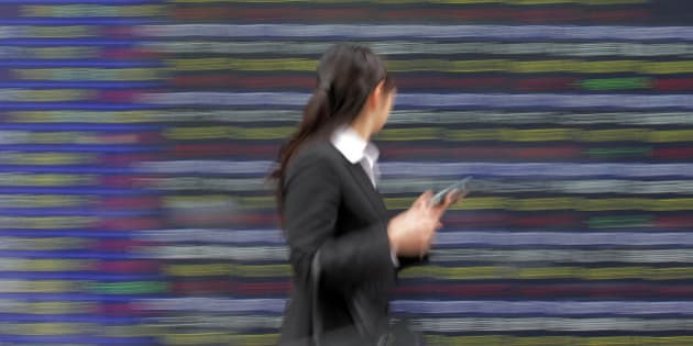 A woman walks past the electronic stock board of a securities firm in Tokyo Wednesday, June 6, 2012. Asian stock markets perked up Wednesday after U.S. service companies, which employ most of the American workforce, grew at a slightly faster pace in May. (AP Photo/Itsuo Inouye)